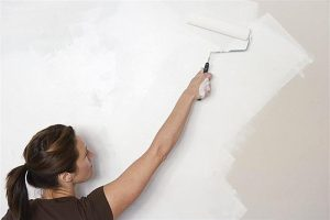 5 tips to prepare your home for showing. Woman painting a wall.