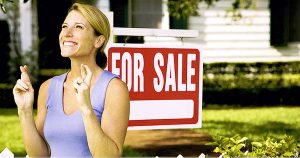 Establishing asking price. Woman with fingers crossed standing in from of home for sale sign.
