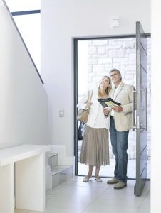 First impressions. Couple standing inside doorway admiring home.